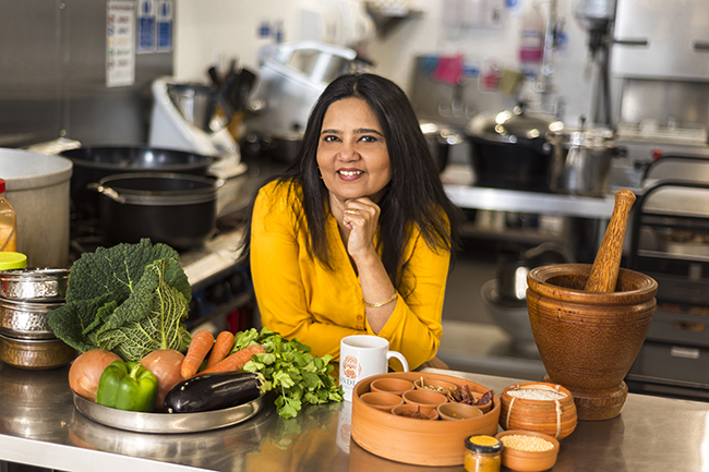 Mandira in a lovely yellow top smiling, ready with her spices and fresh ingredients